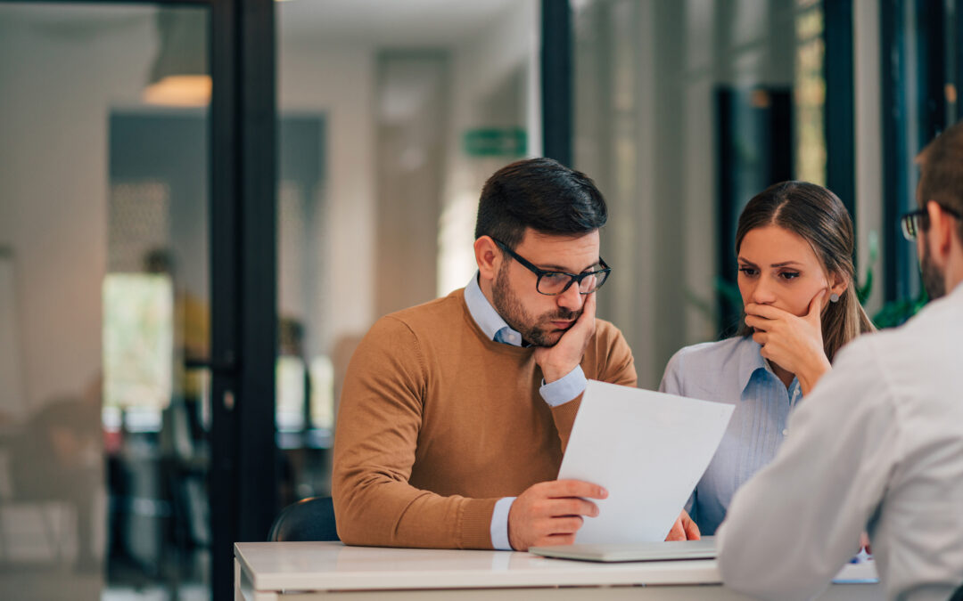 Financial adviser with young couple at banking meeting